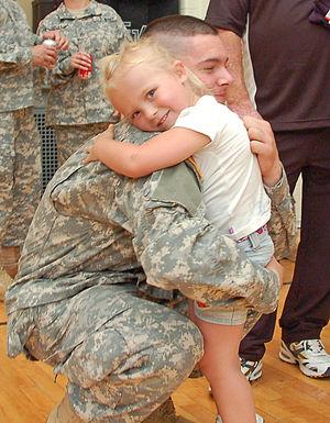 Pvt. Scott Mix, a student, hugs his niece at t...