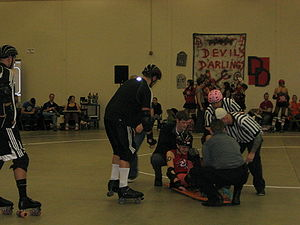 EMTs tend to a roller derby athlete who suffer...