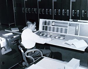 A meteorologist at the console of the IBM 7090...